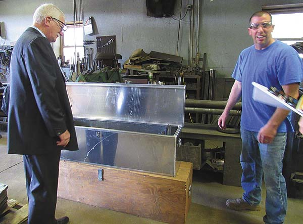 shop foreman Ryan Sowle shows Ronald Peters a metal storage box the company produced for the Fulton County Sheriff